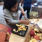Preschool student cutting apples