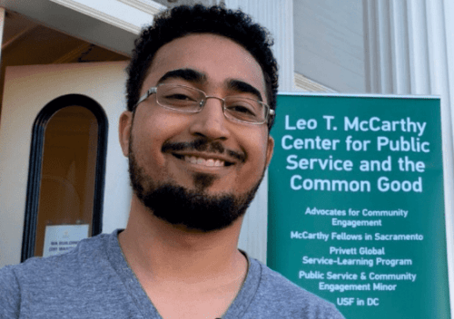 Photo of Graduate Student in front of McCarthy Center Banner