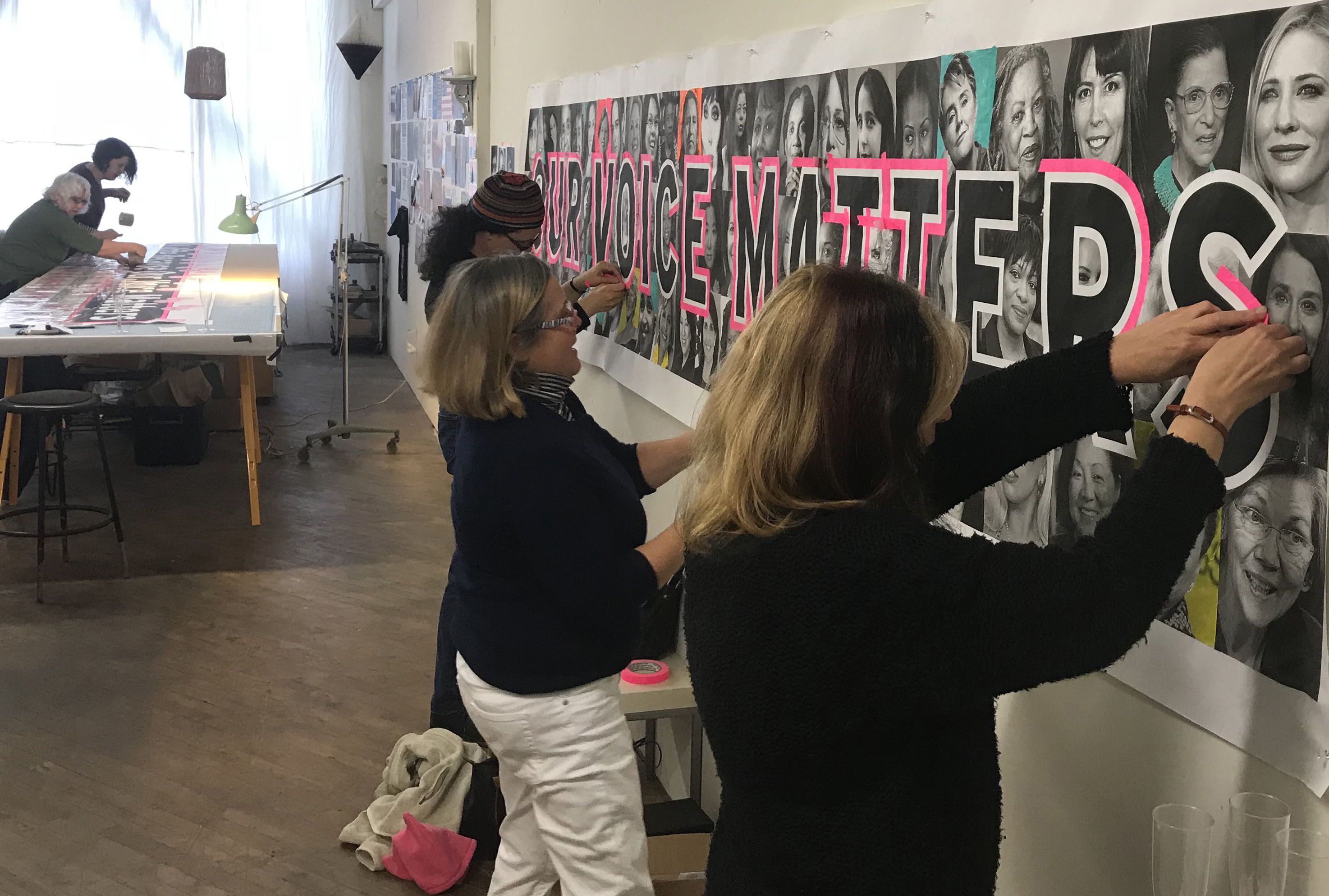 Volunteers outline bold letters in pink tape to increase visibility for the march.
