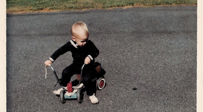 blond toddler in a dark blue sailor suit on a pushbike