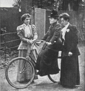 19th-century photograph of F. Willard on her bicycle Gladys, supported by two women