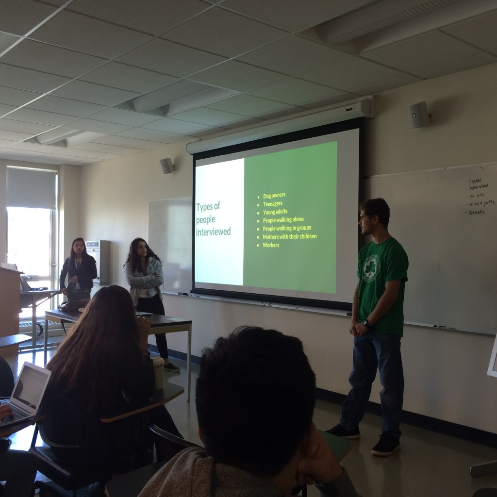 three students standing before a powerpoint slide with information about interview subjects
