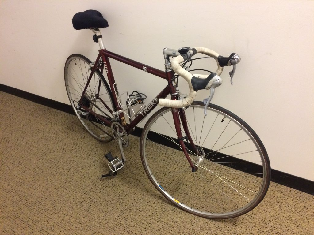 maroon road bicycle with white handlebar tape