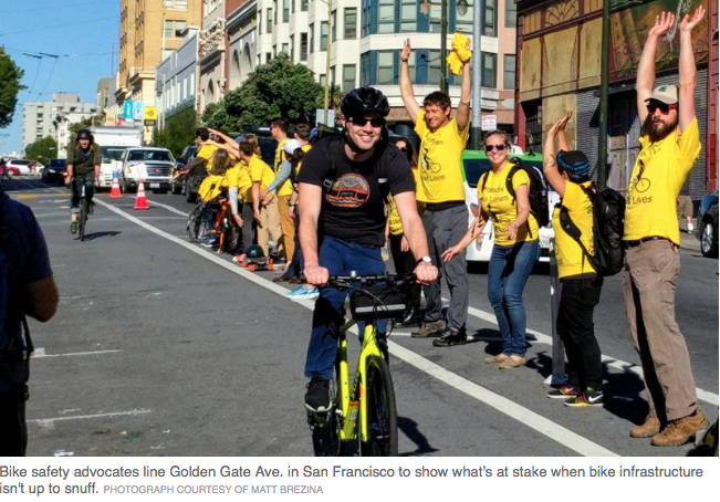 people in yellow shirts forming a human fence between bike lane and automobile lane