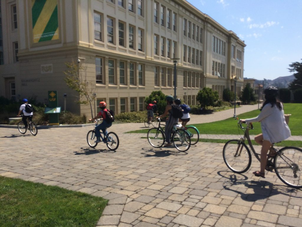 several coms195 students biking by Kalmanovitz Hall, a large classroom building on the USF campus