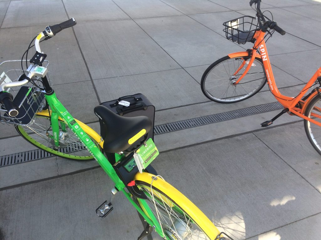 two brightly colored bicycles, one bright green and yellow, the other orange