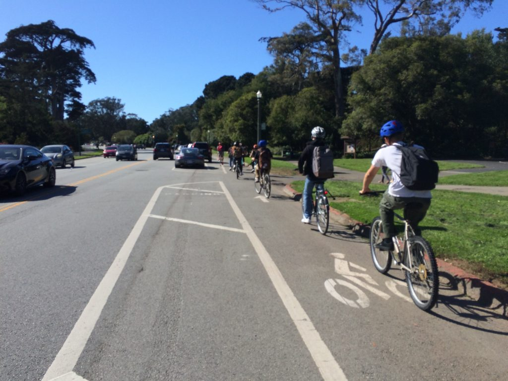 students on bicycles riding in bike lane on John F. Kennedy Drive