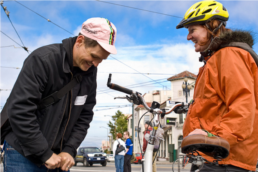 man in a pink cycling hat using a pump to inflate a bicycle tire, smiling woman in bike helmet  watches
