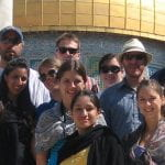 A group of tourists standing in front of a religious site.