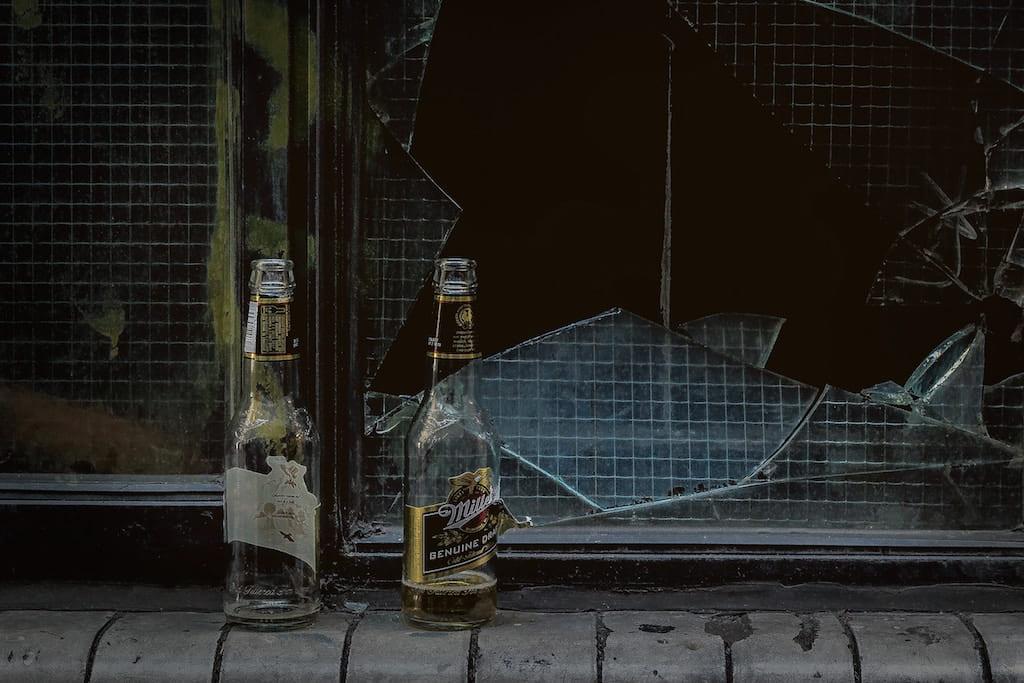 Empty glass bottles in front of a broken window