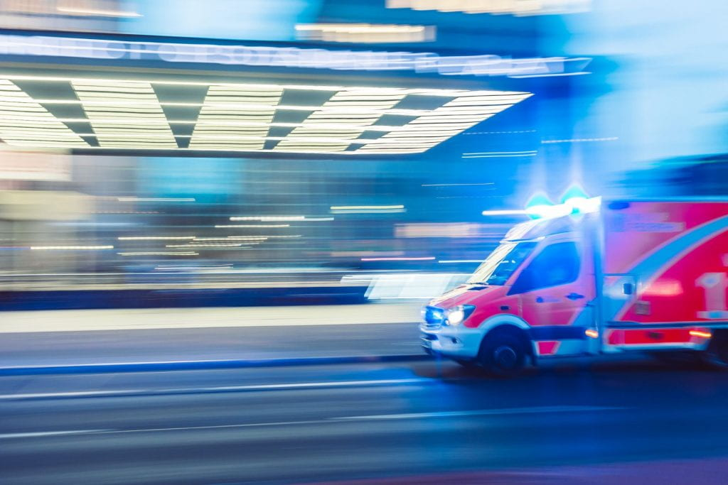 red emergency response vehicle with sirens on in timelapsed photograph