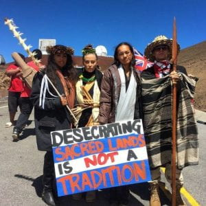 """Mauna Kea Warriors with a sign that reads """"Desecrating sacred lands is not a tradition""""."""