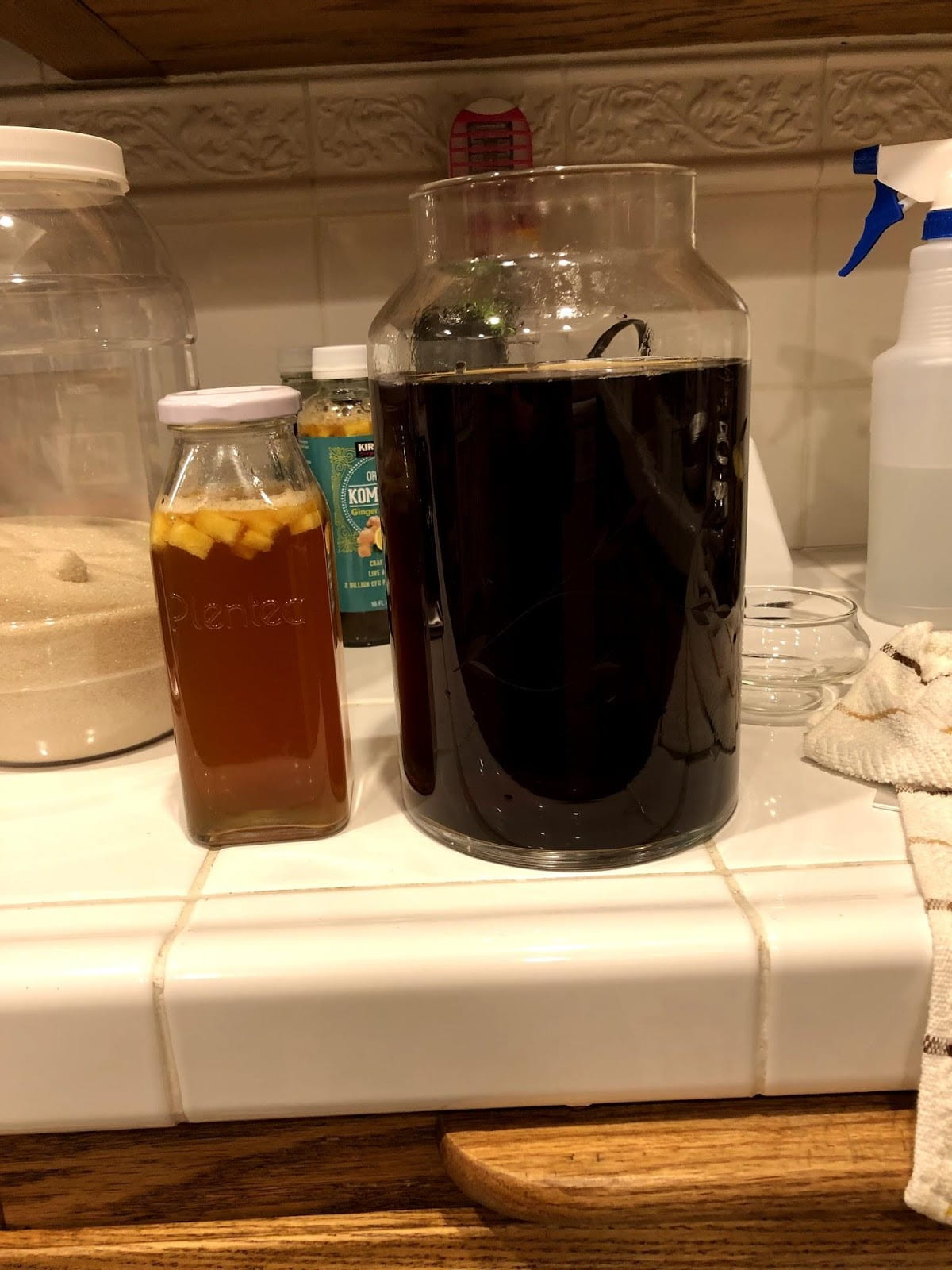 A glass and a pitcher of kombucha.