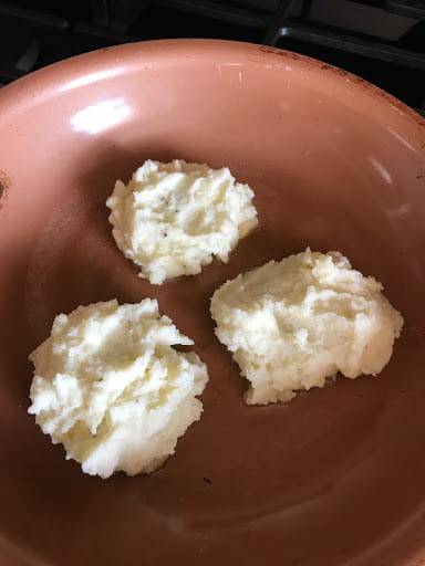 Three dollops of mashed potatoes in a frying pan.
