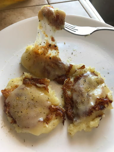 Melted cheese on three mashed potato dollops with a fork pulling on the melted cheese.