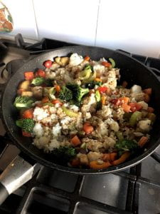 Rice and vegetables in a frying pan.