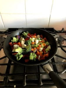 Vegetables and spices added to a frying pan.