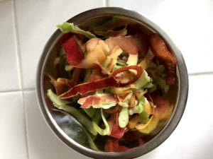 A bowl full of apple peels and other scraps.