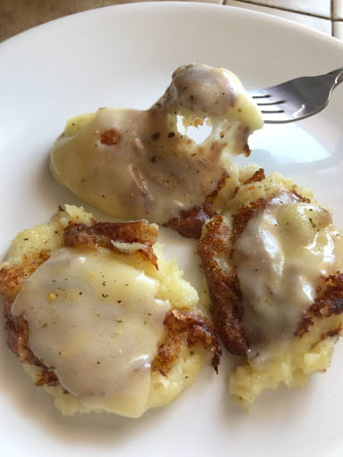 Melted cheese on three mashed potato dollops.