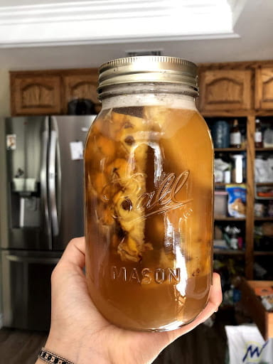 A hand holding up a sealed jar of tepache with white foam near the lid.