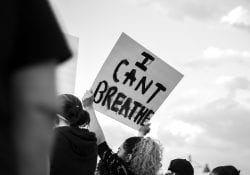 Crowed protest sparked by George Floyds death with sign reading I Can't Breath