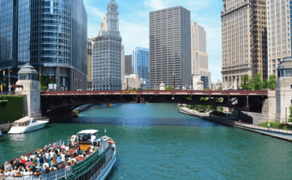 Image of the Chicago river with bridge and a tour boat