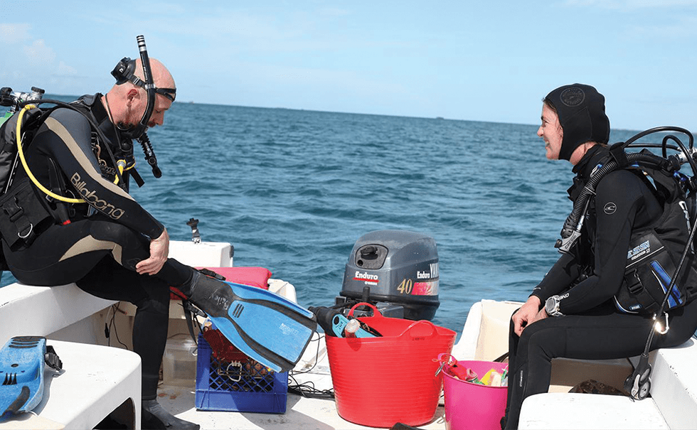 Image of two researchers wearing wetsuits and sitting on a research boat
