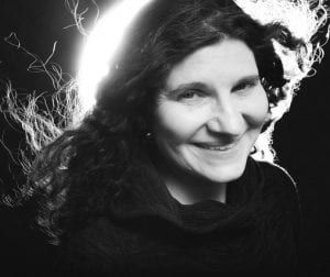 This is a black and white photo of Leslie Buxbaum-Danzig. She is backlit and wearing a turtleneck top. She is smiling and has curly hair.