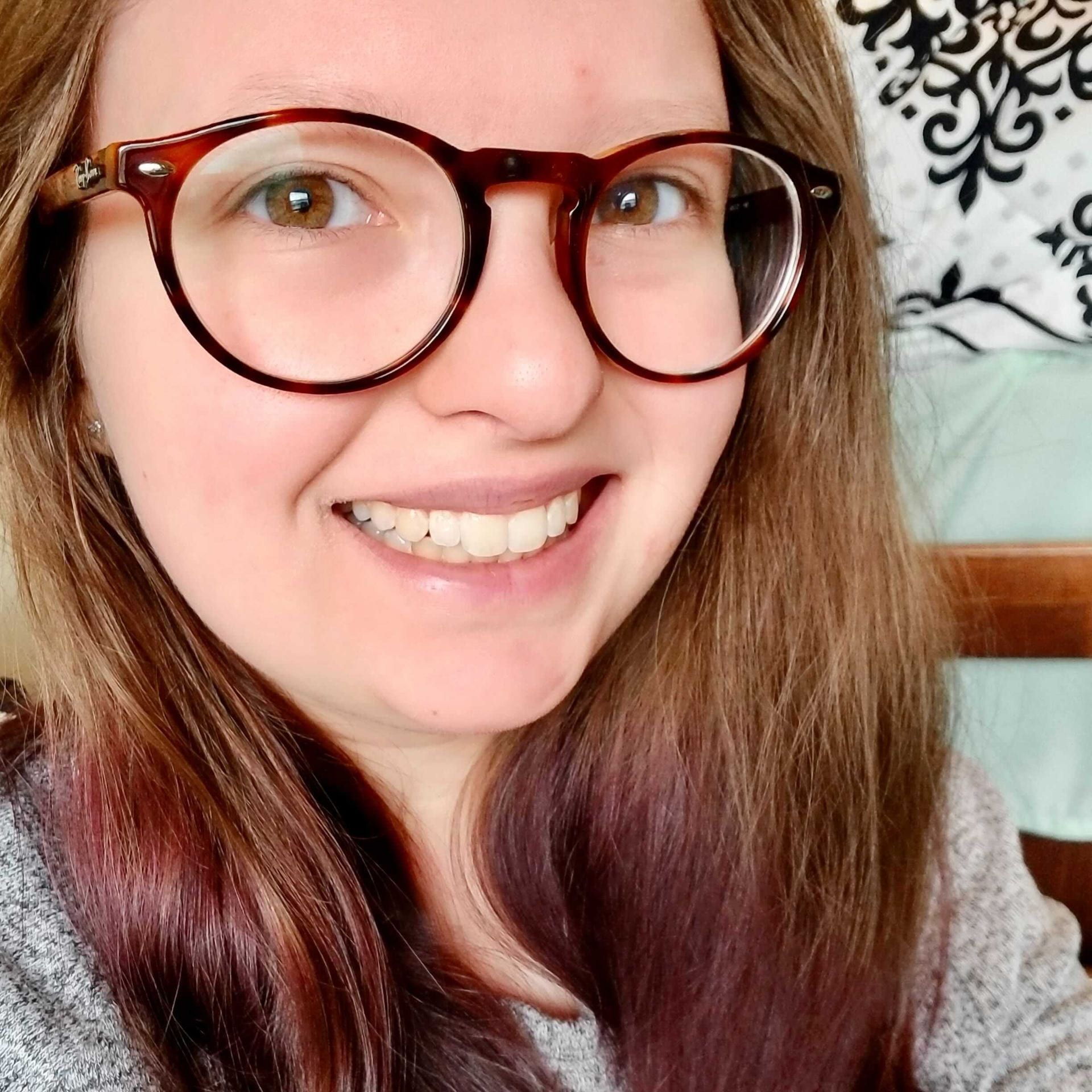 Photograph of Cassie Manrique, she is looking at the camera, smiling and wearing glasses