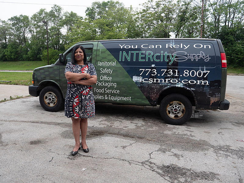 """African American woman in dress stands in front of a van reading """"You Can Rely on Intercity Supply"""""""