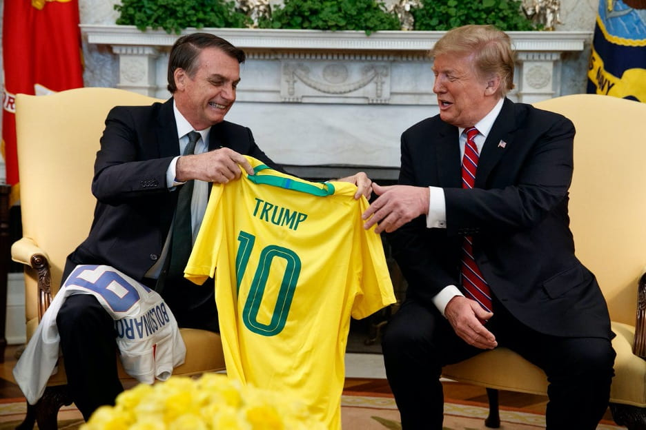 Jair Bolsonaro hands yellow soccer-style t-shirt to Donald Trump during a meeting.