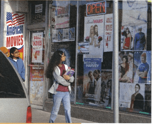 Two young women walking by a storefront while looking at the window advertisements.