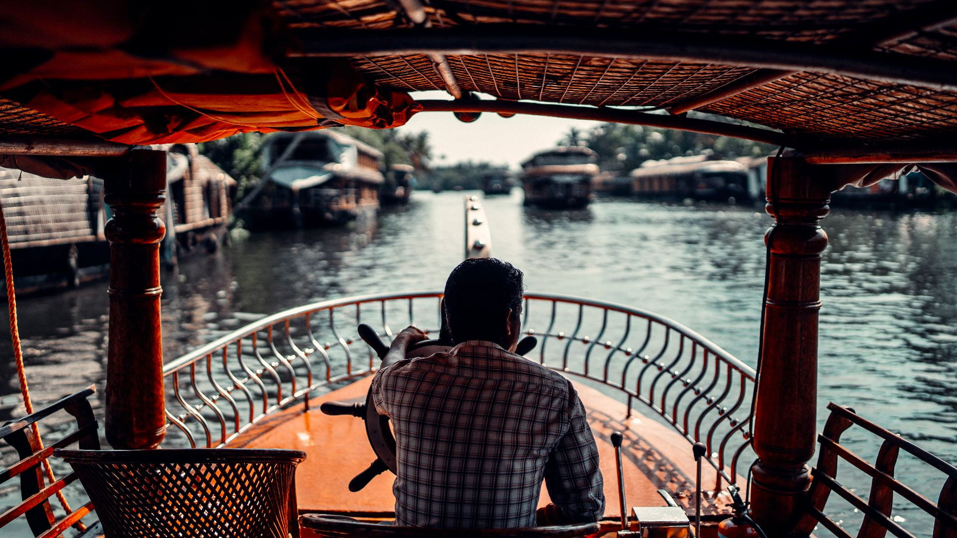 Man driving a boat in Kerala, India