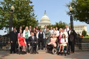 Group of AAPD interns standing or sitting in wheelchairs with the Capitol Building in the background