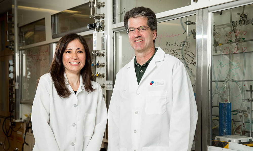Two people in labcoats, standing