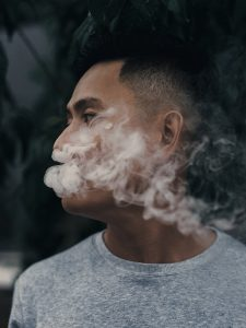 Asian American with smoke coming out of mouth