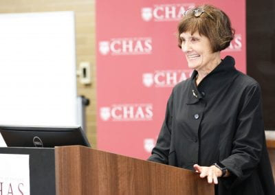 Jeanne Marsh standing at a podium and smiling at the 2019 CHAS Paris Conference
