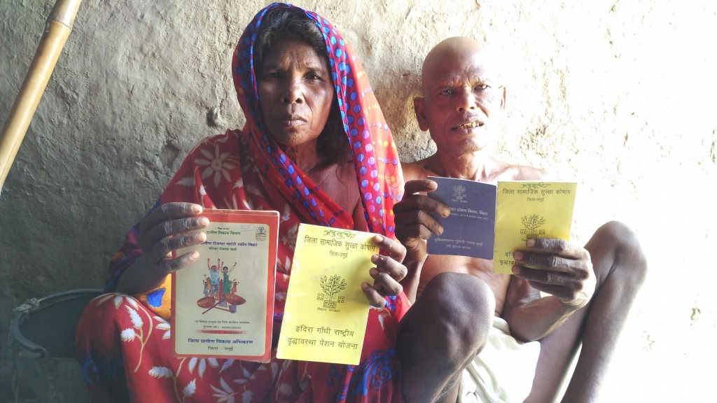 "Phoolkumari Devi and Vaso Manjhi, an old Mahadalit couple in Ganesh Nawada village, Jamui, with their NREGA Job Card (""labour card""), both their old age pension cards, and their NFSA Priority Card. They recieve 10 KG grain every month from the PDS."