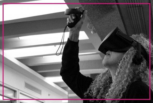 Black and white image of a woman with gray, curly hair using a virtual reality set