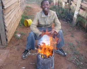 This boy is cooking his food outside because he does not have electricity or gas. - Mfundo Klaas