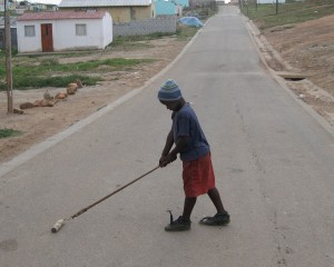 This boy does not have friends to play with. He is playing with the roll for painting. When there are no playgrounds, many kids have to play alone. - Anele Bokuva