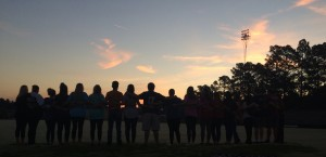 """Facing the sunrise, a group of seniors stands with their arms around each other. Many students looked forward to seeing Kristin Koonce. """"I went to hear Kristin speak,"""" senior Destinee Aaron said. """"She makes my day and she's very good at motivating people."""""""