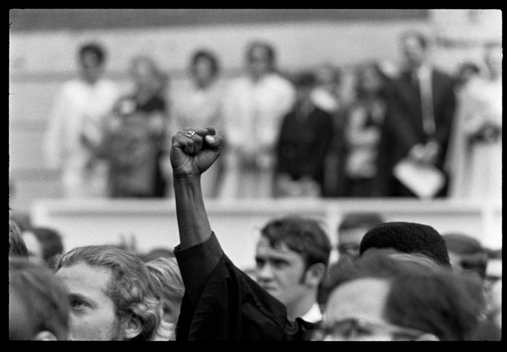 A Black Power fist raised at Commencement 1969.
