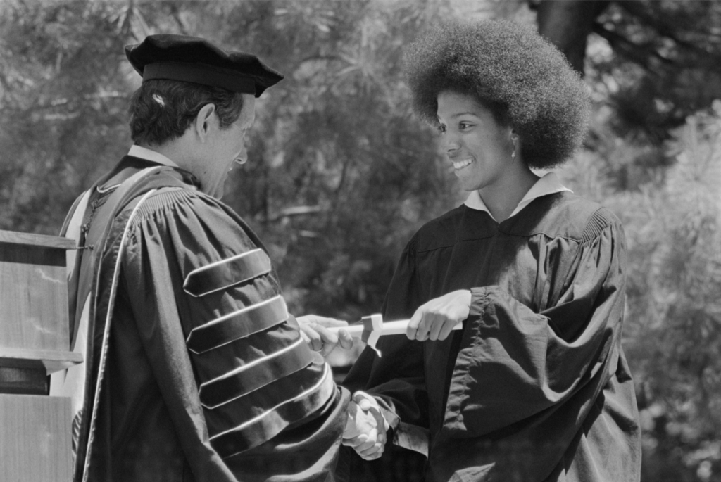 black and white photograph of Lucia Butts receiving her diploma