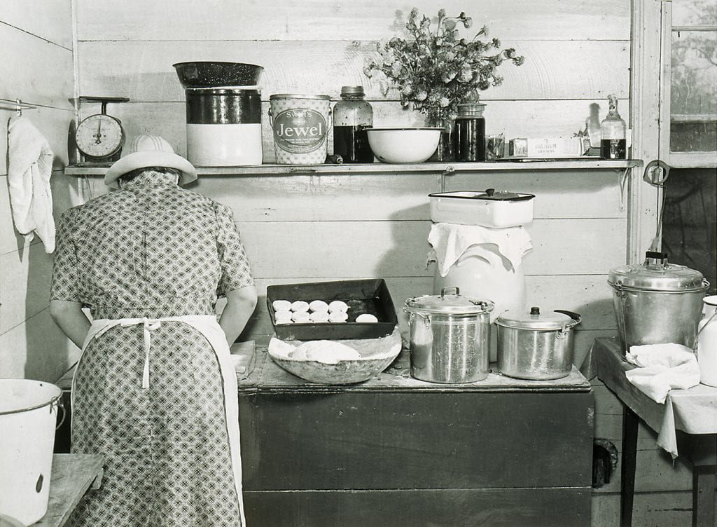 black and white photograph of a woman in apron standing in front of table with biscuits in pan, dough rising, and cooking pots