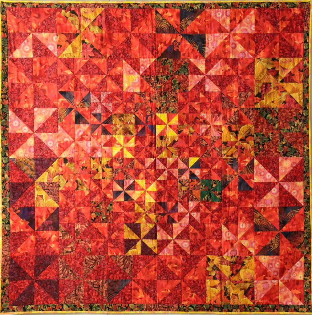 Quilt with triangles of fabric, primarily in shades of red with some yellow mixed in, arranged in pinwheel patterns