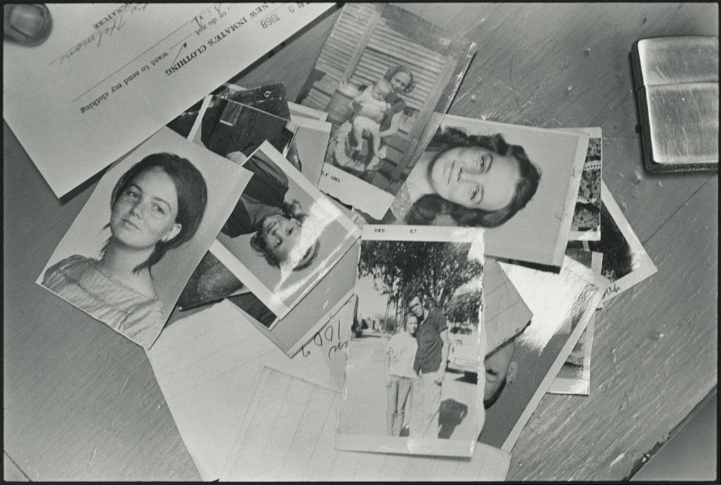 Black-and-white photograph of snapshots, including portraits of young white women, in a pile, with a lighter, scraps of paper, and a form labeled New Inmates Clothing