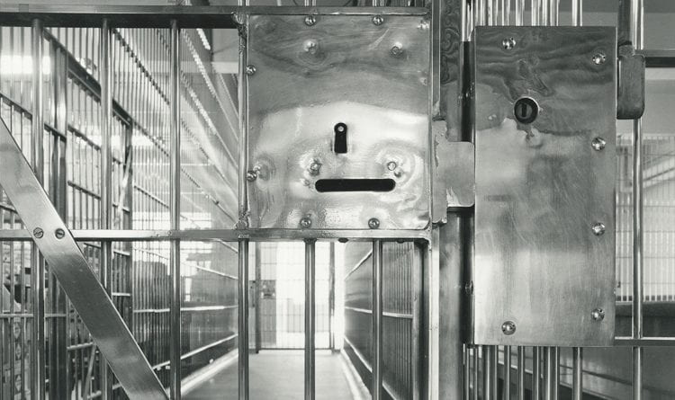 Black-and-white photograph focused on the lock on a door with bars leading to a hallway of prison cells