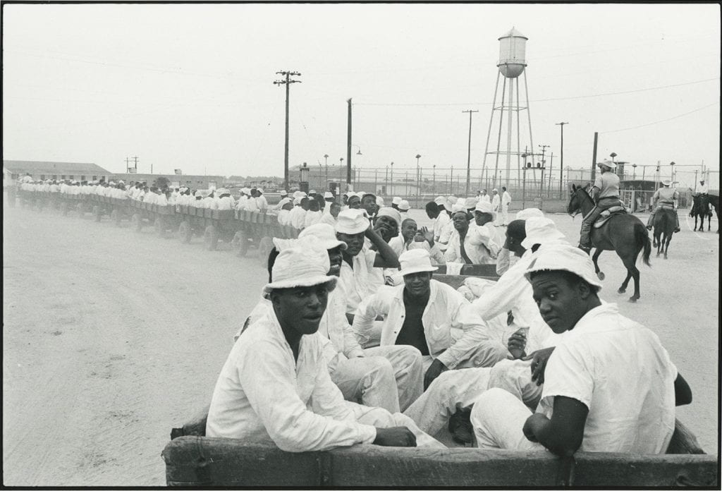 Black-and-white photograph of dozens of Black men being transported in a long train of wooden carts, three prison guards on horseback nearby