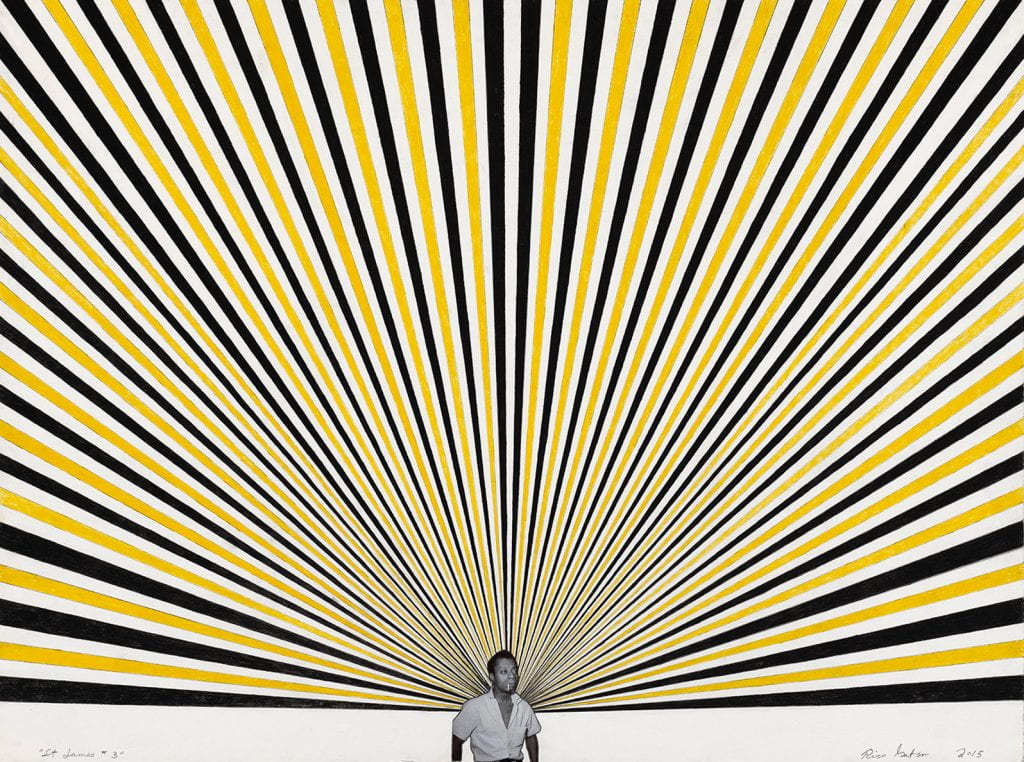 man smoking cigarette stands in front of a painting of rays of yellow and blue rays fanning out above him